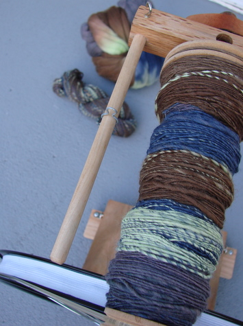 bobbin with skein and top in the background